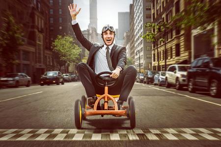 Happy Businessman auf einem Pedal Auto
