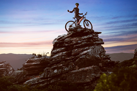 Person with his bike on the top of a mountain