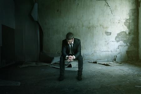 Smashup man zit depressief op stoel Stockfoto