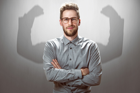Empresario sonriente con brazos musculares sombra Foto de archivo - 76919559