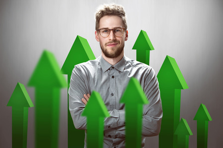 Smiling Businessman with green arrows pointing upwards