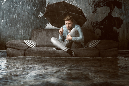 El hombre en su piso inundado Foto de archivo - 76974374
