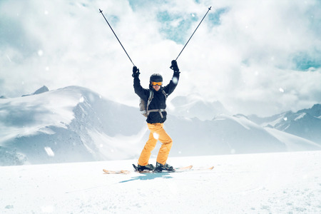 Happy Skier in front of a mountain landscape