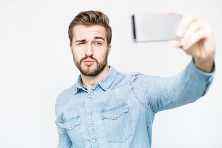 Handsome Man nimmt ein Selfie mit Smartphone Standard-Bild - 77022289