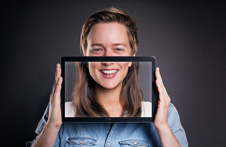 Match half faces with a tablet screen while smiling Stock Photo