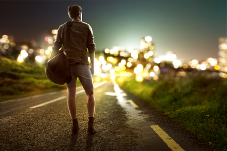Guy walks towards city lights on a country road