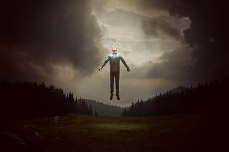 man levitating infront of hills
