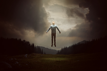man levitating infront of hills