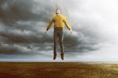 Floating man with disintegration effect 스톡 콘텐츠