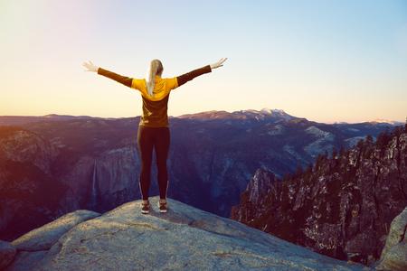 Sporty woman on mountains peak Imagens