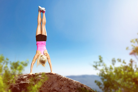 Sporty woman performs a handstand Stock Photo