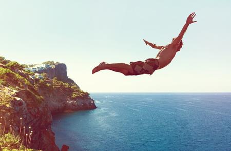 Mann springt von Klippe ins Meer Stock Photo