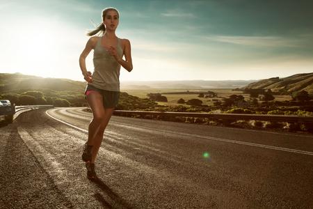 Frau läuft im Sonnenuntergang Stock Photo