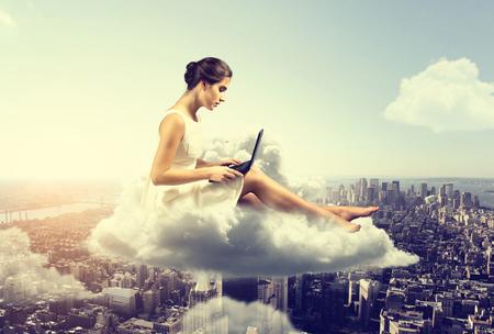 Femme travaillant o nuage au-dessus de la ville Banque d'images - 77466335