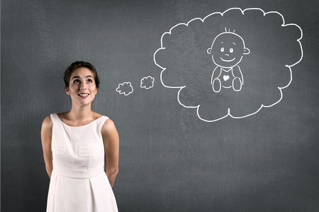 Woman thinking about a baby in a thought bubble Standard-Bild