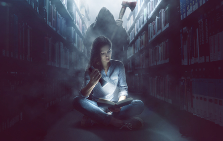 Frau liest ein Buch in der dunklen Bibliothek Standard-Bild