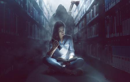 Vrouw leest een boek in donkere bibliotheek