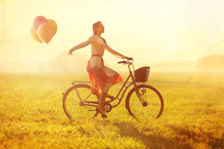 soulfulness: Woman on a Bike with balloons Stock Photo