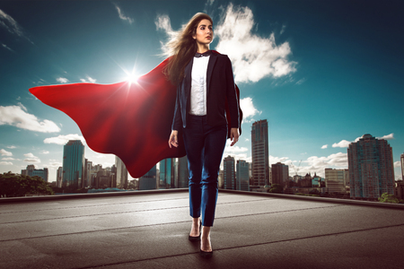 Superwomen with red cape on a roof