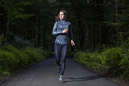 Runner woman in a dark forest