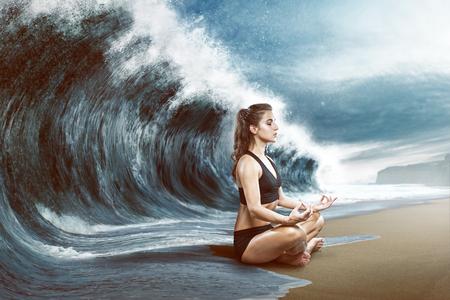 女性は、大きな波の前でくつろぐ 写真素材