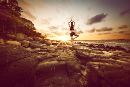 Woman meditates on rocks by the beach Stock fotó - 77466877