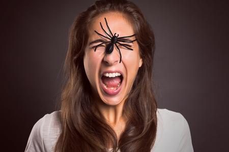 psique: Mujer con araña en su cara Foto de archivo