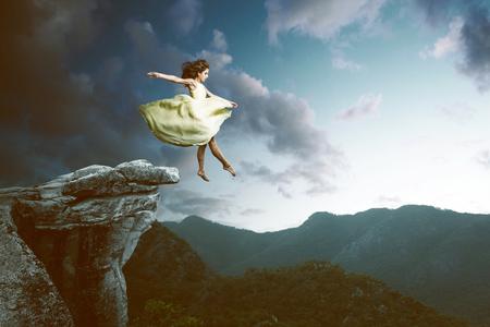 Frau springt aus einem hohen Felsen