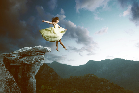 Woman jumps from a high rock Stock Photo