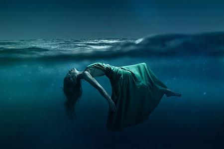 Woman floating underwater