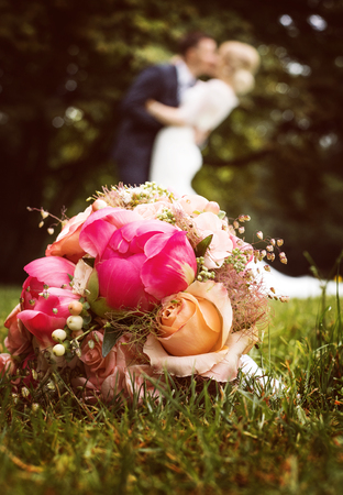 Bride and groom kissing behind bouquet of flowers