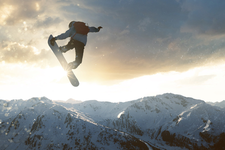 Snowboarder jumping in front of mountains