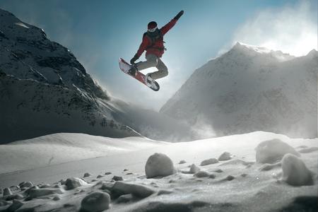 Snowboarder sautant devant les montagnes