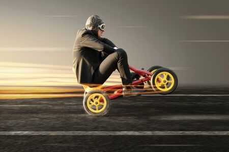 Businessman doing a wheelie on a pedal car 版權商用圖片
