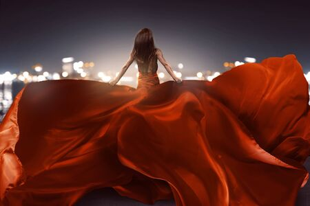 Woman with red dress in front of bokeh lights