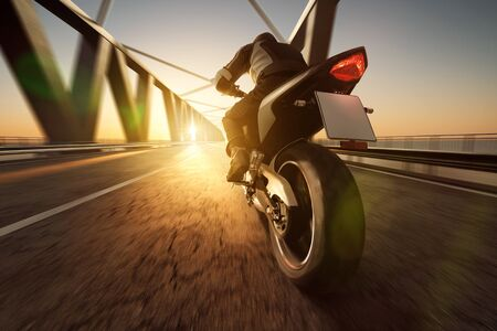 Motorcycle on a bridge during sunset