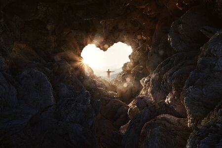 Man stands at heart-shaped opening of a cave and spreads arms