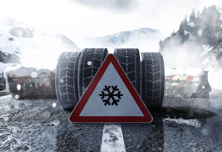 Winter tires and road sign on a smooth road