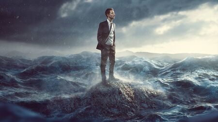 Businessman standig on a rock in the surf