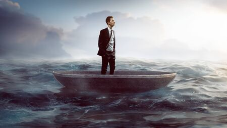Businessman in a small boat swimming on the sea