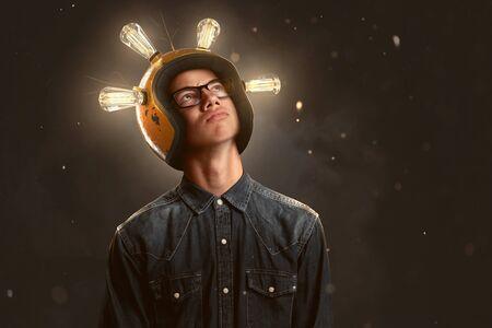 Smart teenager wears a lightbulb helmet 스톡 콘텐츠