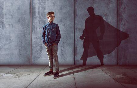 Adolescente con l'ombra del supereroe Archivio Fotografico