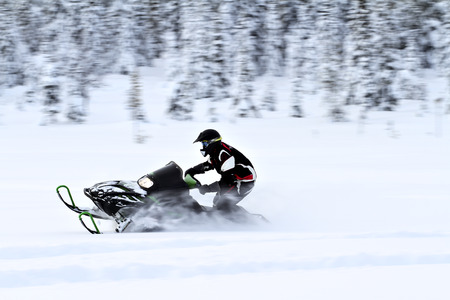deep powder snow: A snowmobile in high speed in the forrest close to the polar-circle Stock Photo