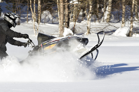 deep powder snow: High speed and swirling snow from a snowmobile Stock Photo