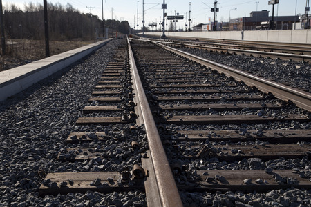 encircling: A railway track from a low angle with some  buildings encircling