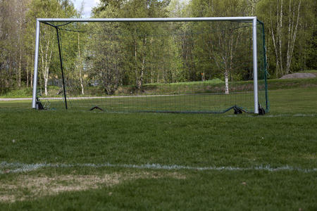 low perspective: An empty soccer goal from a low perspective with some trees in the background Stock Photo