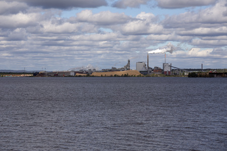 clody: A factory with some water in front and a clody sky