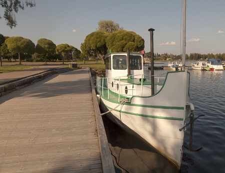 tress: A ship moored to the dock and some tress in the background