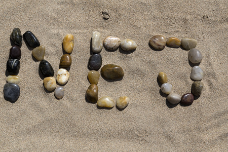 A set of pebbles in a sandy beach forming the swedish word for No.