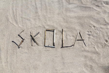 pedagogic: A set of pebbles in a sandy beach forming the swedish word for school